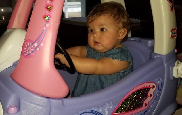 infant girl riding plastic vehicle